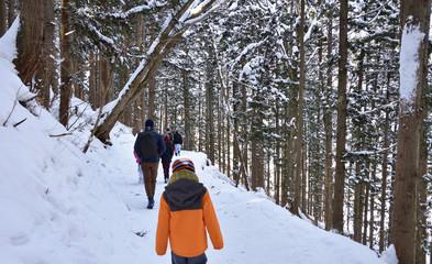雪の山道を歩く人々