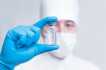 the doctor holds a medical ampoule, a test tube with a clear liquid