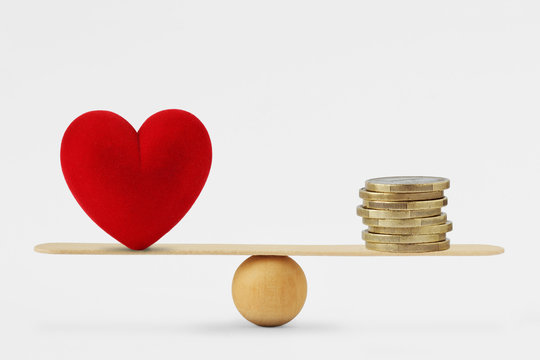 Heart and money on balance scale - Order of priority in life among love and money