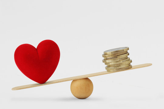 Heart and money on balance scale - Concept of love priority in life