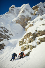 Two climbers on a snow-covered mountain slope in the background rocky ridge. Tilt-shift effect.