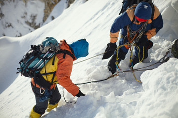 Foto op Aluminium Alpinisme Two climbers on a snow-covered slope in the mountains closeup.