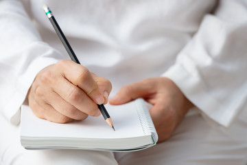 Hand writing on note pad..Woman hands holding  note pad and  black pencil writing on blank paper ,front view..