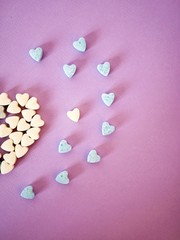 Half a big heart from small heart tablets, sweet vitamins on tinted paper, top view, concept of love, health, valentines