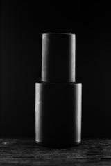 Black gel nail polish in a black tube on a black background