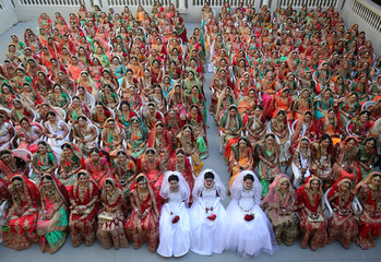 Brides pose for a group photo before taking their wedding vows during a mass marriage ceremony in Surat
