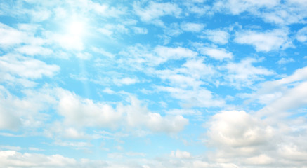 Bright sun on blue sky with clouds. Wide photo .