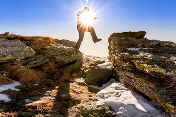 man jumps among the rocks, standing out against the sun