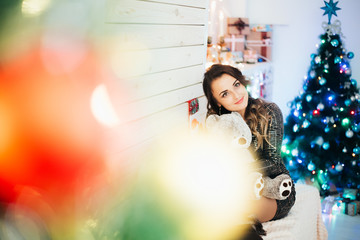 Beautiful girl with a bear in her hands on the background of lights and Christmas tree