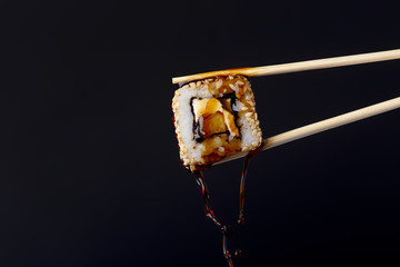succulent roll between chopsticks on black background, drops of soy sauce dripping from sushi, food background, Japanese cuisine