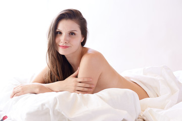 brunette woman lying on bed in bedroom
