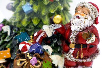 Glass ball with snow along with Santa Claus and gifts