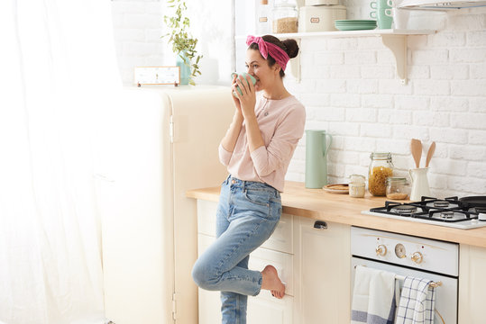 Young woman drinking a morning coffee in kitchen