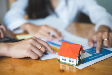 House interest, real estate agent working in modern office with small house model house buying and loan concept.