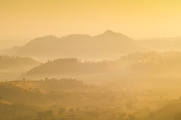 sunrise at Doi Mae Salong, beautiful mountain view misty morning of the hills around with soft mist and colorful of yellow sun light in the sky background, Chiang Rai, Thailand.
