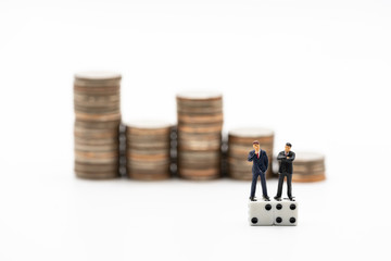 Miniature people:  Businessmen thinking on dice with coins stacks as background. Financial, risk, chance, and business concept