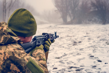 A military soldier with a Kalashnikov assault rifle conducts aimed fire at the enemy in winter, dressed in camouflage to prevent the enemy from advancing.
