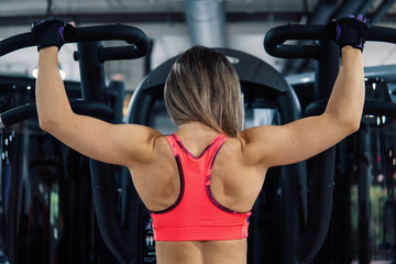 Young fit woman doing shoulders exercise using training machine in gym. View from back.