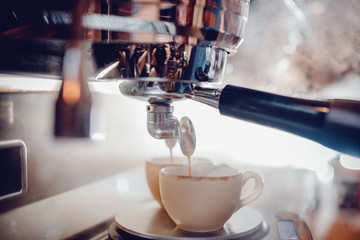 Close up of espresso pouring from coffee machine in two white cup. Professional cappuccino brewing. Background is blurred.