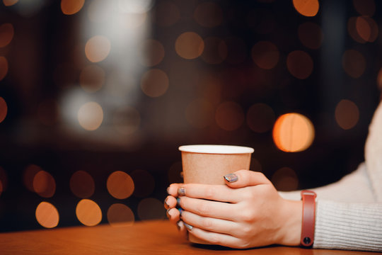 Cup hot tea or coffee in hands of woman with beautiful unusual nail design, manicure, and fitness bracelet.