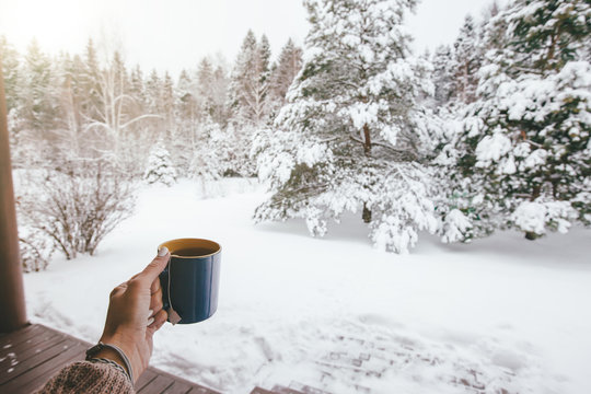 Holding mug with tea over snowy view