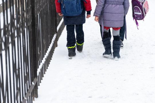 In winter, children return home from school.