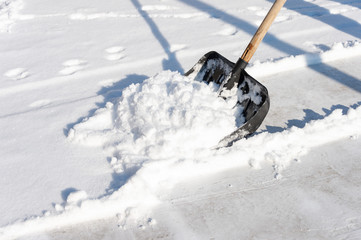 man cleans the snow in the yard