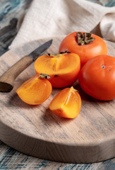 Fresh persimmon fruits on board and knife