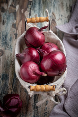 Red onion in small basket on rustic table