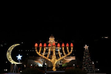 December's holidays symbols in Israel: Christmas tree, Star of David, Hanukkiah and Star and crescent - symbols of Judaism, Islam and Christianity in the German Colony