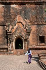 Mujer paseando por el Parque arqueolàogico de los antiguos templos y pagodas de Bagan. Myanmar