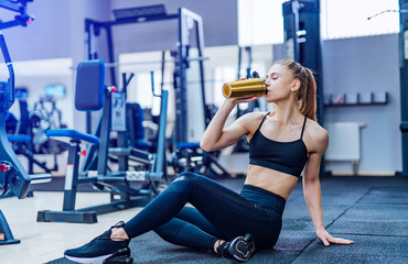 Fitness woman drinking water while sitting and resting on the floor in gym. Woman exercise workout in fitness gym breaking relax and holding protein shake bottle during training.