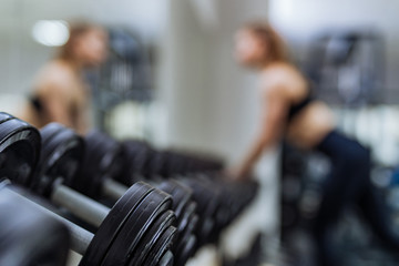 Row of dumbbells near the mirror on the background of sport gym with a female. Close-up. Sports concept and a healthy lifestyle.