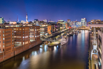 The Harbor District (HafenCity) in Hamburg, Germany, at night. Panoramic aerial view of the Sandtorkai and the Kaiserkai across the traditional port Sandtorhafen.
