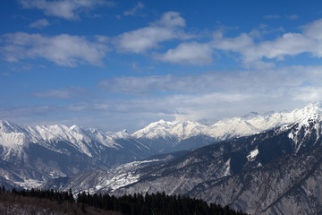 Snowy mountains and blue sky with clouds at winter sun day