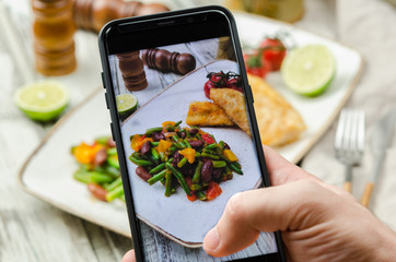 Young man taking photo of fish and vegetables plate on smartphone. Taking food photo with mobile phone.