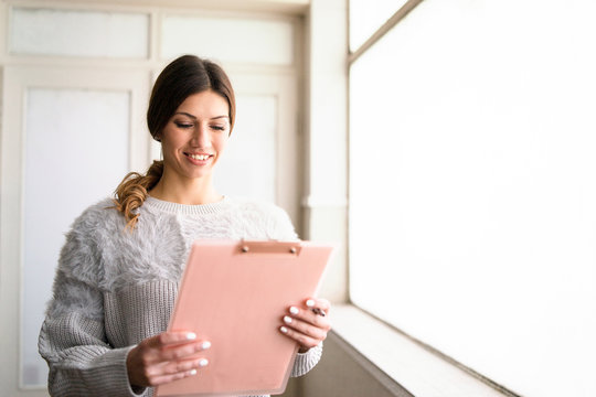 young woman with clipboard at work