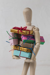 Wooden puppet holding stack / pile of gift boxes on white textured background