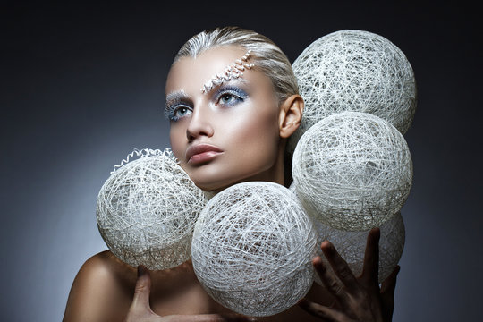 beauty fashion portrait of a beautiful woman with creative makeup on her face. White braided balls around the head of the model.