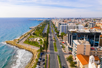 Wall Mural - Aerial view of Molos Promenade park on coast of Limassol city centre,Cyprus. Bird's eye view of the beachfront walk path and palm trees, Mediterranean sea, piers, urban skyline and port from above