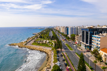 Aerial view of Molos Promenade park on coast of Limassol city centre,Cyprus. Bird's eye view of the beachfront walk path and palm trees, Mediterranean sea, piers, urban skyline and port from above