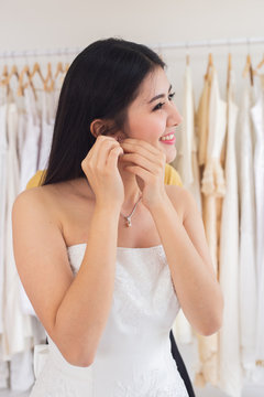Beautiful bride in white wedding dress puts on earring.