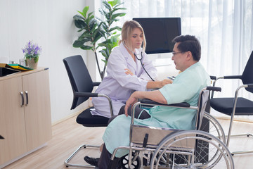 female doctor explaining Male patient symptoms in wheelchair