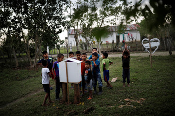 Local children look at an altar with a picture of Jakelin Caal in San Antonio Secortez village