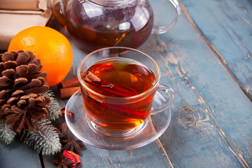 Drink of apple tea with cinnamon stick, star anise and clove. Seasonal punch in cup on wooden background.