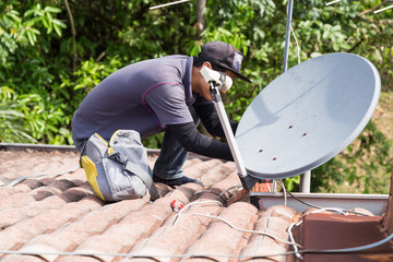 Technician installing satellite dish and television antenna on roof top Fototapete