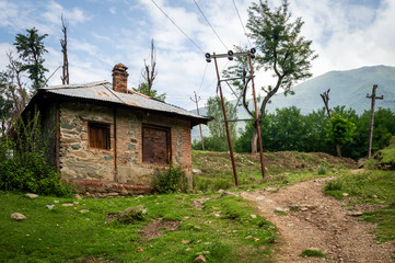 A house on a dirt road in a village in Kashmir