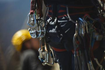 Climbing tools hanging on the climber's belt closeup.