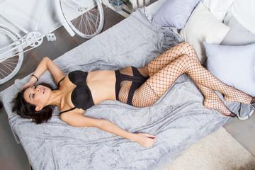 Girl in black lingerie in the bedroom on her bed