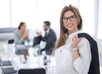 smiling business woman standing with a jacket over her shoulder